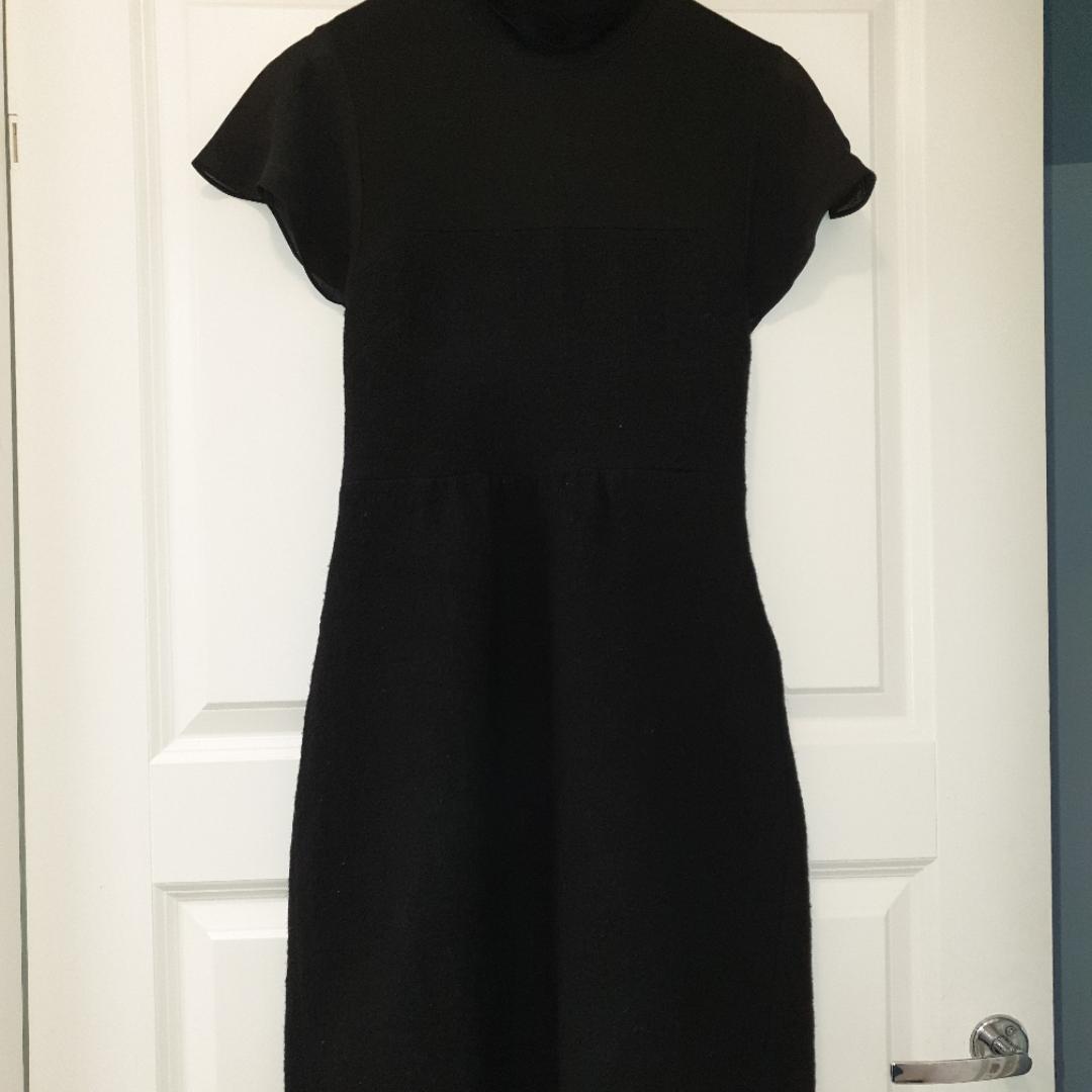 Svart klänning med hög hals kjolen är i tjockare ull tyg . Klänningar.