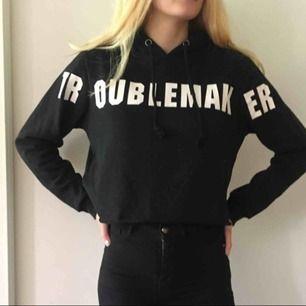 """En svart hoodie med vit text där det står """"TROUBLEMAKER"""" den är ifrån Bikbok. Köparen står för frakten."""