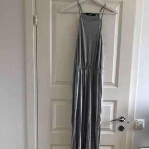Grå maxiklänning med slitsar vid sidorna, perfekt för sommaren. Använd runt 10 gånger, är i bra skick. Kommer från Bik Bok. Möts i Stockholm eller köpare står för frakt.