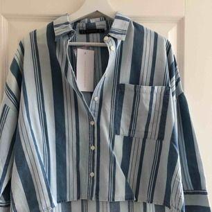 Snygg, blå skjorta i randigt denim-liknande tyg. Oanvänd, lappen och en medföljande knapp sitter fortfarande på. Är i super skick. Märket är DÍLVÍN men köpt på Chiquelle. Möts i Stockholm eller köpare står för frakt.