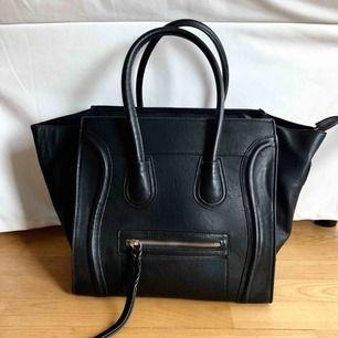 Snygg svart handväska som går att göra större och mindre! Fodret inuti är sammet!