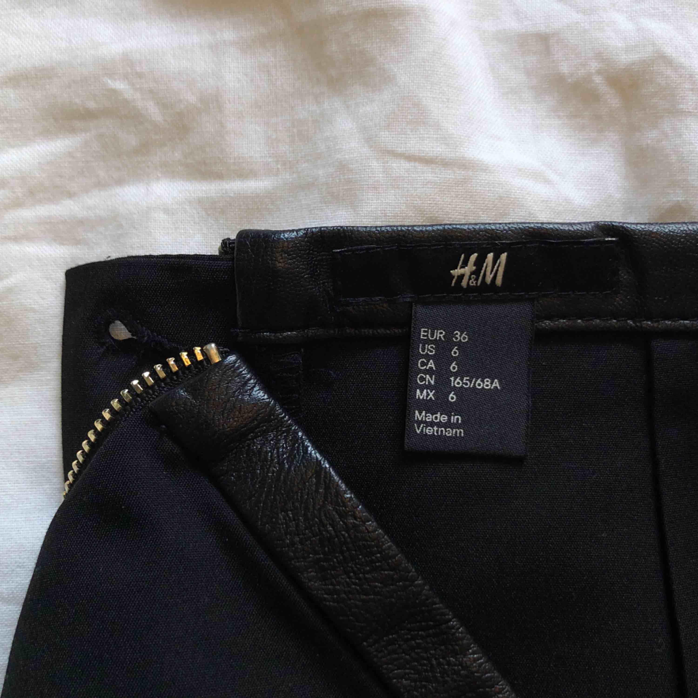 Svart figurnära kjol med fake skinn detalj och dragkedja bak.   Mycket bra skick!   Material 49% Bomull 48% Polyamid 3% Elastan  Upphämtning centrala Uppsala Porto tillkommer vid frakt, 36kr. Kjolar.