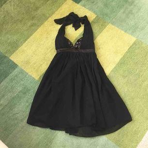 Vacker klänning från Lipsy. Vadderade kupor med paljetter. Glansigt bälte och bakstycke och fint fall i chiffong.