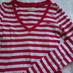 Röd och vit randig v-ringad tröja från hollister. Det som ser grått ut på bilden är bara skuggor. Pris kan diskuteras. Möts upp i Stockholm, om frakt önskas bjuder jag på frakten