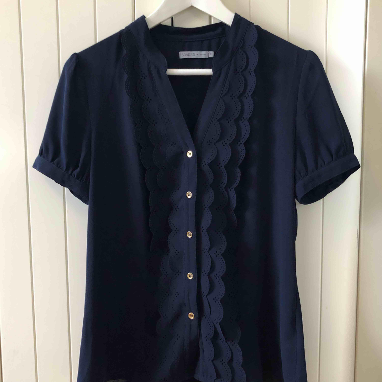 Marinblå blus från Soaked in Luxury, endast använd ett fåtal gånger.  Nyskick!   Material 100% Polyester   Upphämtning i centrala Uppsala Porto tillkommer vid frakt, 36kr. Blusar.