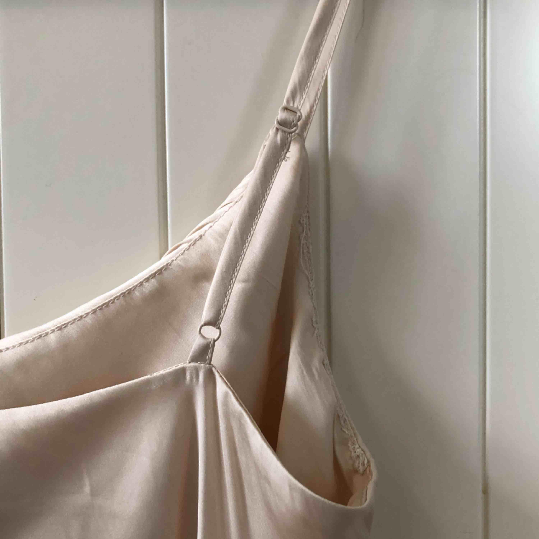 Aldrig använt! Champagne färgat linne med reglerbara axelband.   Material 100% Polyester   Upphämtas i centrala Uppsala Porto tillkommer vid frakt, 18kr. Toppar.