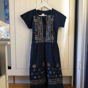 Vintage!  Marinblå klänning med markerad midja och vackra broderier framtill, enfärgad rygg. Dragkedja i sidan och litet knäppe fram. Upphämtas i centrala Uppsala. Porto tillkommer vid frakt, 54kr