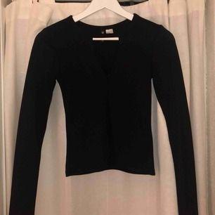 En fin svart tröja från H&M i storleken XS. Den har en liten svart V-ringning som gör tröjan passar utefter tillfälle. Passar till både fest & vardags.  50:- + frakt.