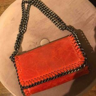 Liten handväska i äkta läder köpt i Italien. Fin röd färg och går att använda banden på två sätt.