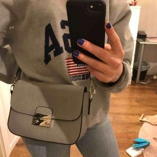 Rymlig handväska från märket Anna Field. Ingår två olika band till väskan.