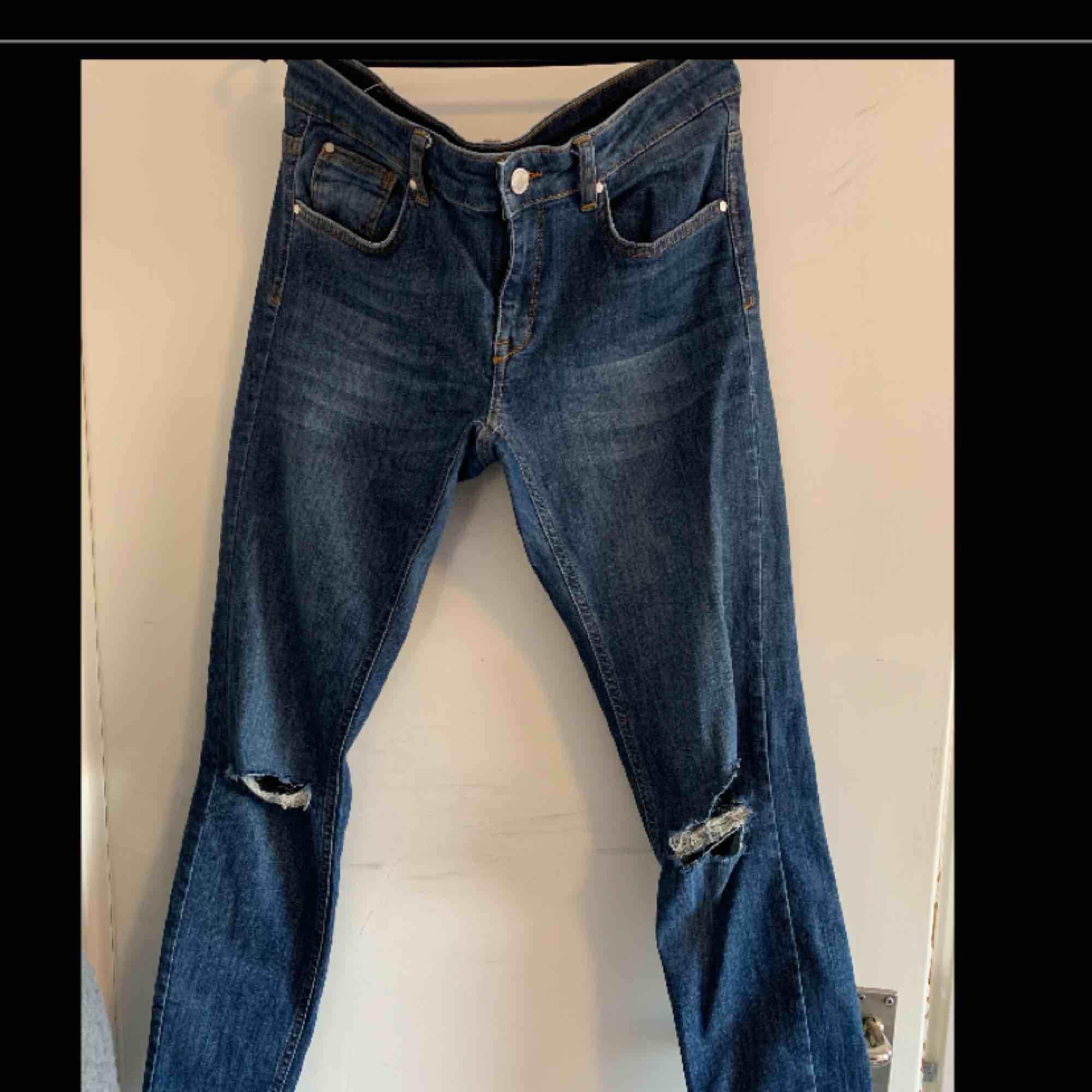 Blåa jeans med hål i båda knäna och slitningarna längst ner på byxorna.. Jeans & Byxor.