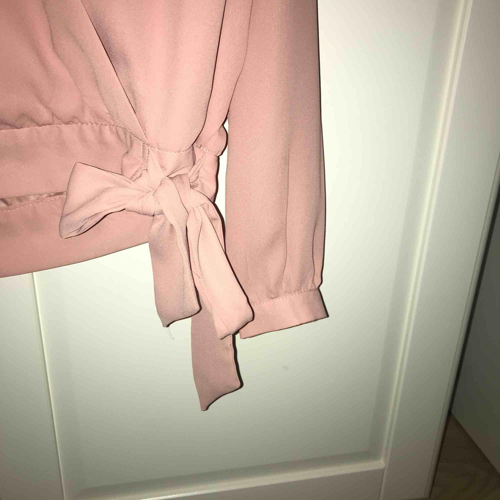 Rosa omlott blus med knytning i midjan. Sparsamt använd. . Blusar.