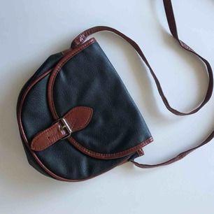 Vintage väska i fakeläder. Fack med dragkedja på insidan. Väskan är 18x18 cm och axelremmen är 120 cm. Frakt ingår i priset!