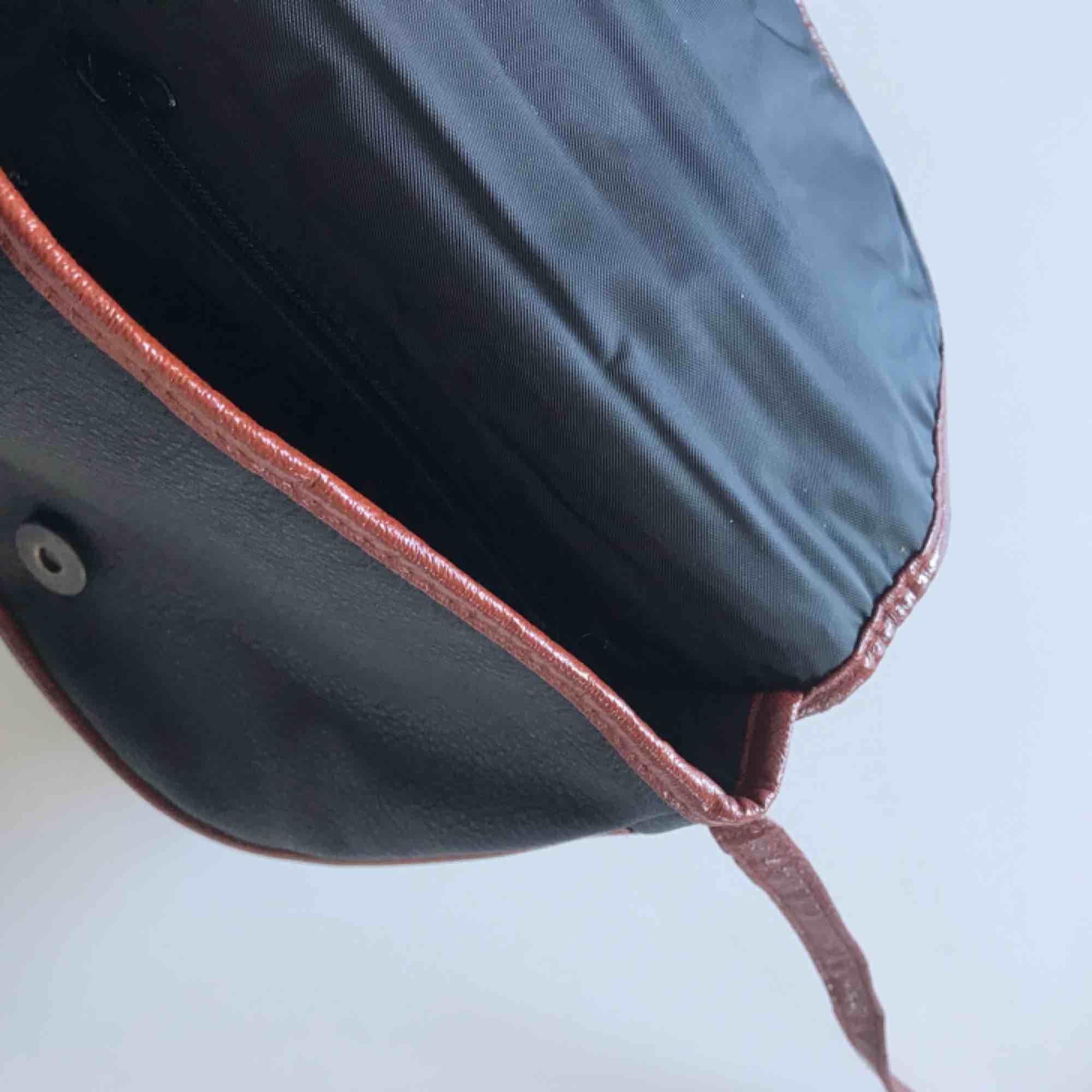 Vintage väska i fakeläder. Fack med dragkedja på insidan. Väskan är 18x18 cm och axelremmen är 120 cm. Frakt ingår i priset! . Accessoarer.
