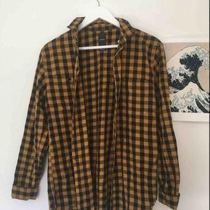 """Rutig skjorta i färgerna svart och gul. Jag har aldrig använt den och den är i bra skick. Är snygg att ha både som  en traditionell skjorta och som """"jacka"""" att slänga på sig. Hör av dig vid eventuella frågor om pris eller plagg!"""