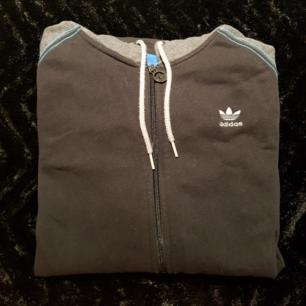 Adidas zip-up hoodie. Svart med gråa ärmar och luva, samt blåa sömmar. Använd fåtal gånger.  Se profil beskrivning för mer info inför köp.