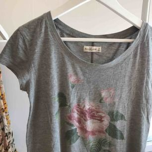 Supersnygg grå t-shirt med blommotiv från det fina märket Abercrombie & fitch. Säljer pga använder ej. Kan mötas i Uppsala, men annars står köparen för frakten.