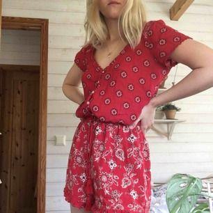 Röd blommig jumpsuit från hollister, knappt använd