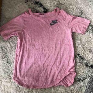 En Nike träningströja i rosa som även visar en del av axeln och är jätte skön