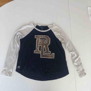 En långärmad grå och marinblå tröja. Med Ralph Lauren märket i brunt, på bröstkorgen. Ordinarie pris- 300