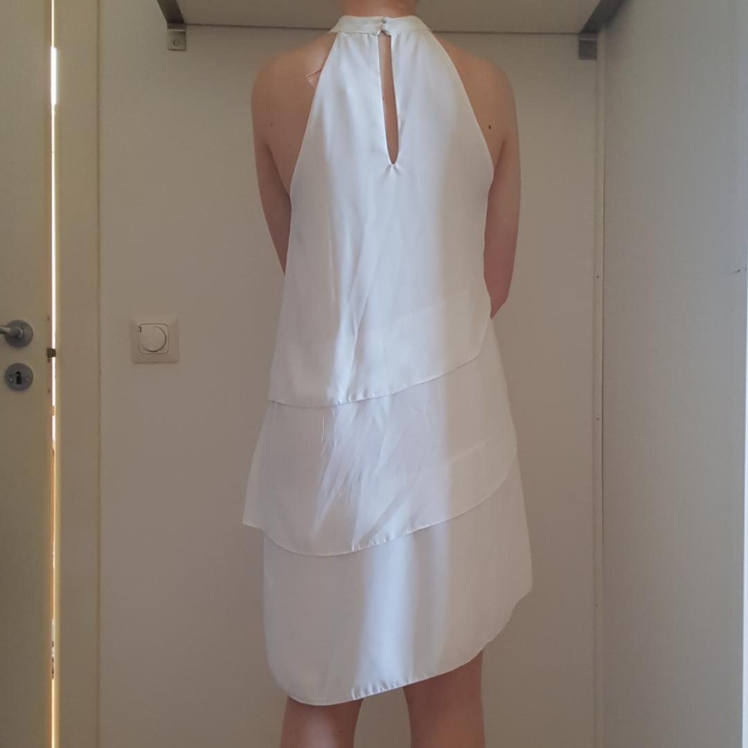 Vit knälång klänning med volanger och hög krage. Fint skick då den är oanvänd!. Klänningar.