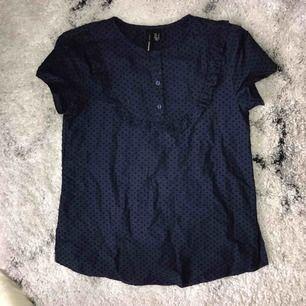 En söt liten blus som är marinblå. Den har volanger vid bröstet samt tre knappar som man kan öppna. Från Mango