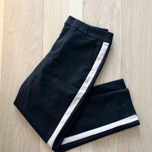 Säljer ett par snygga svarta ankellånga kostymbyxor med en beige rand på sidan!