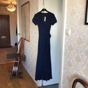 Underbar blå klänning med arm Som du kan knyta i midjan på vänster sida. V-ringad.  Inköpt från asos inför en bal. Aldrig använd pga inköp av annan klänning. Vackert böljande och väldigt skön. Perfekt för sommarfesten , bal eller bröllopet!🌺🔆😍
