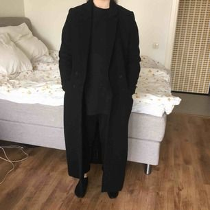 En svart kappa som går ner till anklarna.  Knappt använd! Jag som har på mig kappan är 168 cm lång.  Nypris: 1100 kr