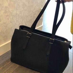 En svart väska med 3 olika fack, varav ett för dator.