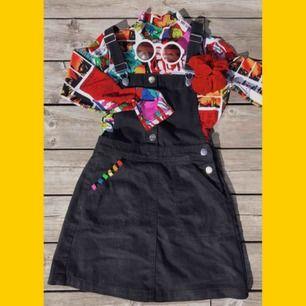 Hängselklänning i svart jeans med knappar och fickor på framsidan
