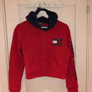 Röd cropped hoodie från Tommy Hilfiger. Köpt på urban outfitters för 1000kr, finns inte längre att få tag på och är använd endast en gång. Säljer på grund av att jag tyvärr vuxit ur den.