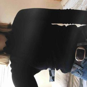 Takt svart ribbad polo från Gina med detaljer på halsen och armarna.