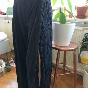 Mörkblåa mjukisbyxor, de är slappa och sköna och har två slitsar vi benen.