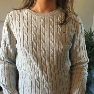 Grå kabelstickad tröja från GANT i bra skick använd några gånger, frakten är på 40kr och köparen står för den.