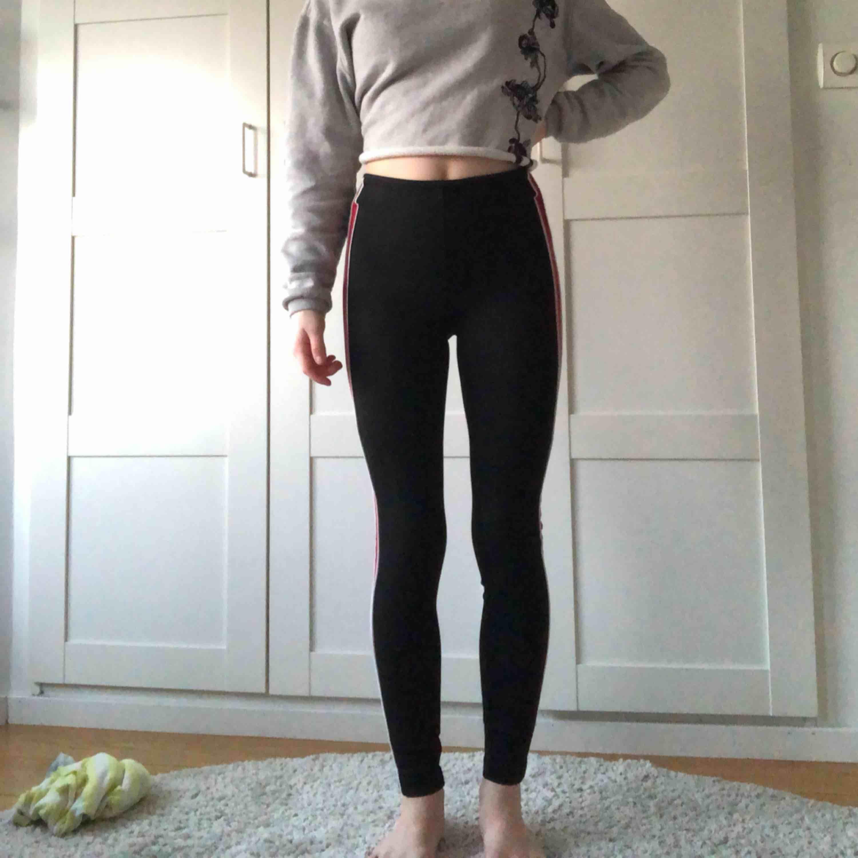 Svarta byxor med en vit och röd rand på sidan. Ordinarie pris- 250. . Jeans & Byxor.
