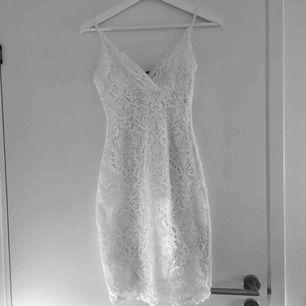 Super vacker vit klänning i spets. Figursydd i modellen och passar både en S och en XS. Näst intill oanvänd. Passar super nu till studenten eller liknande. Skriv till mig om ni önskar fler bilder eller har några frågor :) Frakt betalar köparen.
