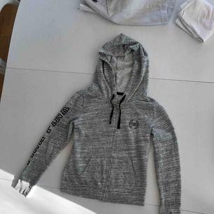 En grå Huddi med luva, ifrån pink med tryck på fram och baksida. Och med paljetter på ryggen. Ordinarie pris- 800 kr.