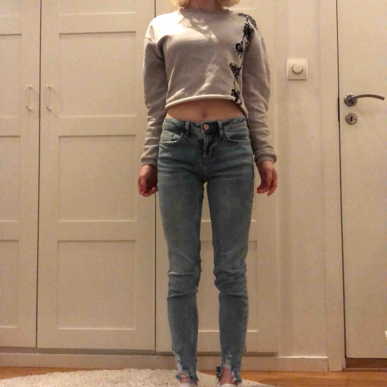 Ett par låg midjade jeans. Som är slitna (trasiga) vid vaden. Ordinarie pris- 250 kr. . Jeans & Byxor.