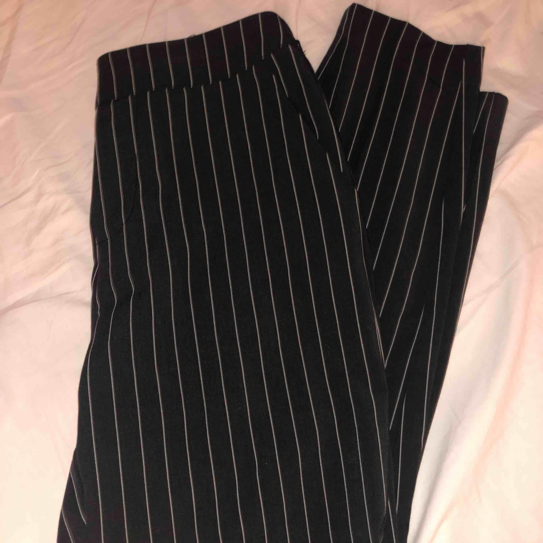 Väldigt snygga svarta kostymbyxor med tunna vita ränder. Resorband i midjan, vilket gör att de sitter väldigt snyggt.. Jeans & Byxor.