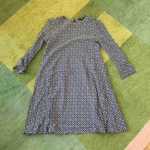 Fin klänning i utsvängd modell och med snyggt mönster. 3/4 ärmar.