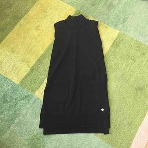 Tuff svart topp/tunika. Polo och snygga fickor framtill. Långa slitsar på sidan. Maska som gått på framsidan (se bild 3).