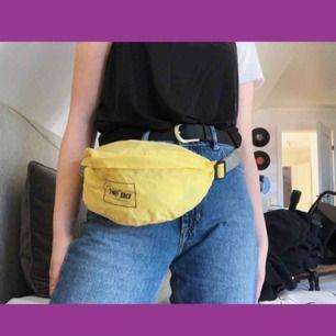En supercool pastell-gul vintage fannypack/magväska ifrån H&M! Har gråa remmar samt grått tryck med svart spänne. Rymlig i ett vattentätt material. Lite större, jag som är ca 70cm över höfterna kan inte ha den runt midjan utan att den hänger lite.