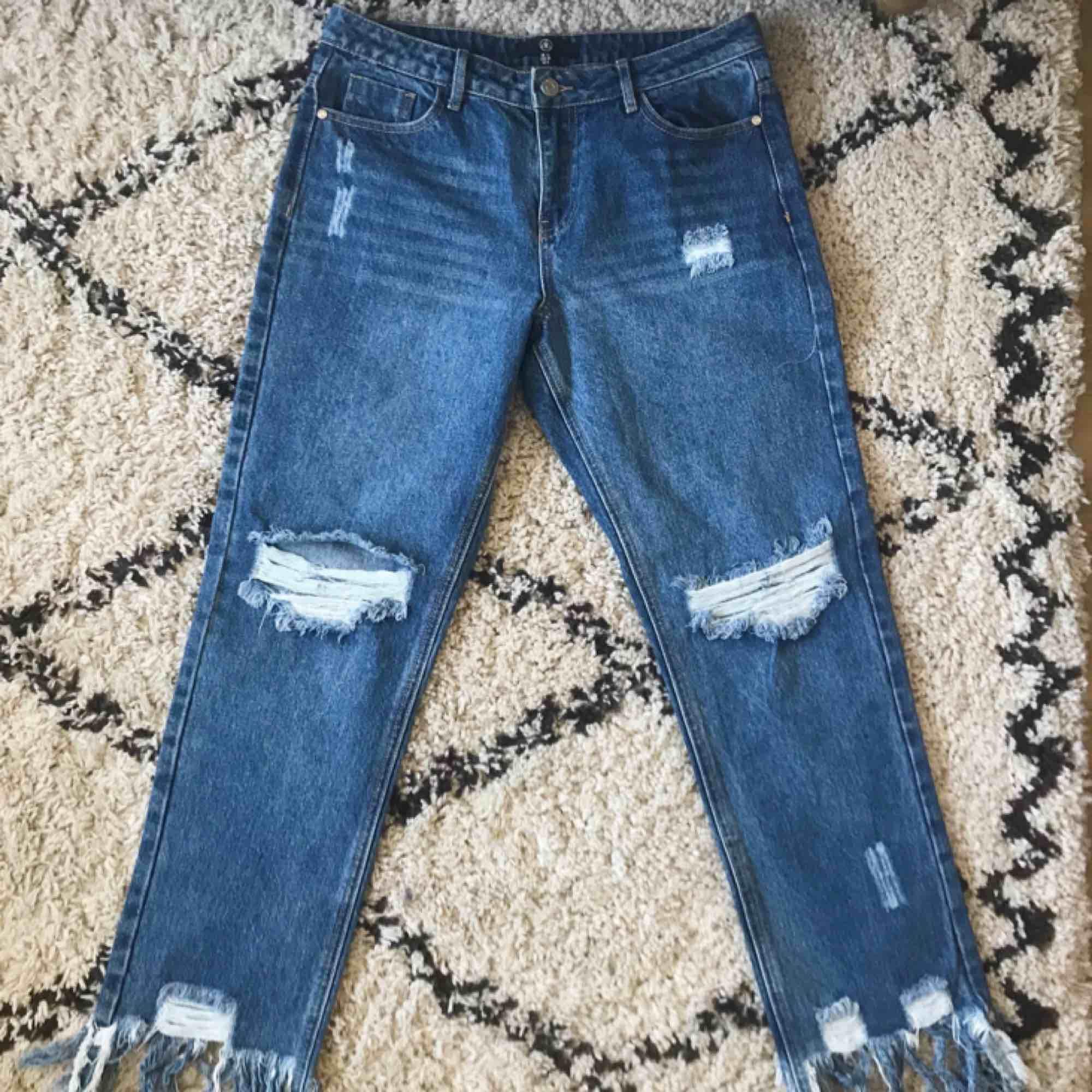 Helt oanvända jeans från Missguided! Håliga med fransar nedtill, mellanblå jeansfärg. Passar bra över lår och höfter på någon som normalt är en medium/26-27a i jeans.. Jeans & Byxor.