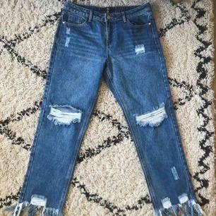 Helt oanvända jeans från Missguided! Håliga med fransar nedtill, mellanblå jeansfärg. Passar bra över lår och höfter på någon som normalt är en medium/26-27a i jeans.
