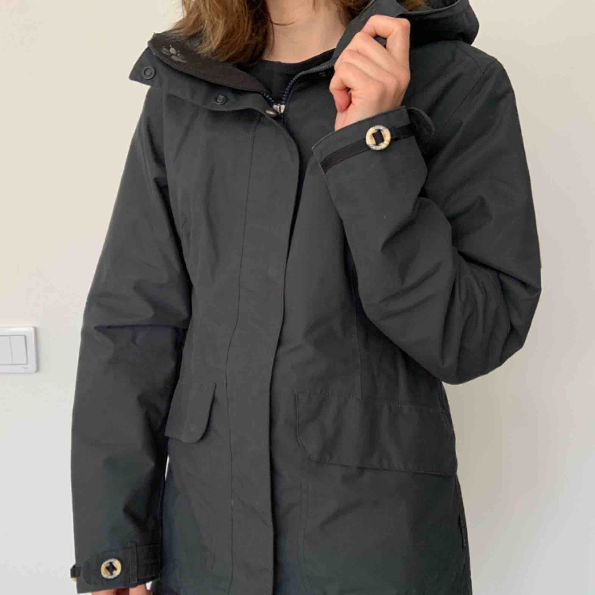 Jacket - waterproof & windproof Brand: Jack Wolfskin Size: S Colour: Charcoal Grey  Lots of nice little details, like wooden buttons.  Breathable. Weatherproof. You can make it tighter in the back.  Lots of pockets.  Hardly ever worn. Great condition. . Jackor.