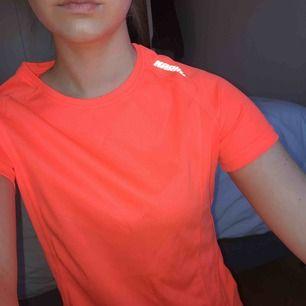 Träningstshirt i neonorange färg, strl XS. Material: polyester. Aldrig använd. Kan mötas upp i Norrköping eller Katrineholm, annars står köparen för frakten ✨