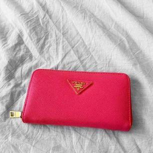 Rosa Prada plånbok i bra skick, förutom att dragkedjan på insidan är svår att stänga. Vet inte om den är äkta eller inte. Frakt kostar 36kr extra, postar med videobevis/bildbevis. Jag garanterar en snabb pålitlig affär!✨ ✖️Fraktar endast✖️