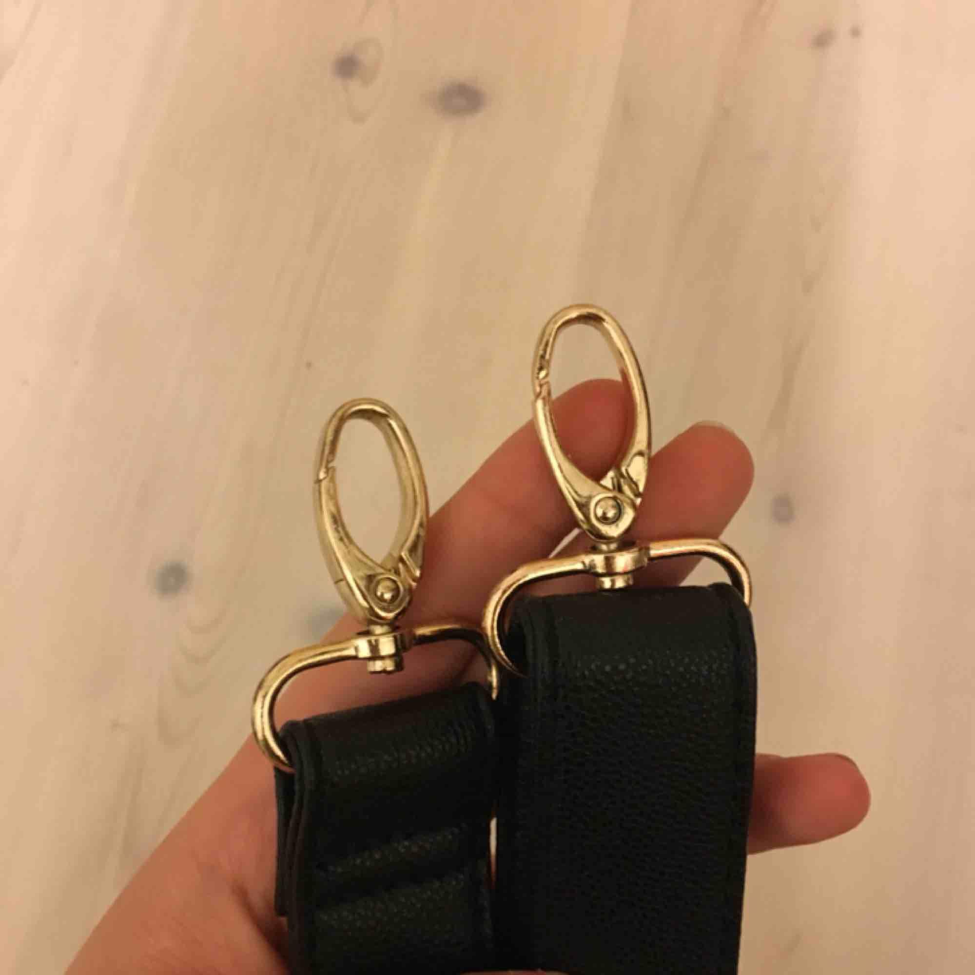Rem till väska i svart fejkläder. 80cm på bilden men man kan justera längden . Accessoarer.