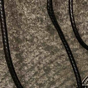 Festligt ockulta halsband i silverfärg på band i läderimitation. Passar häxor, trollkarlar, alla och i Närke.
